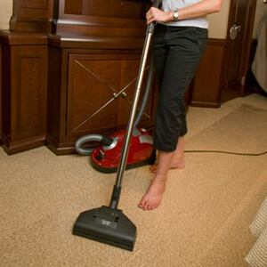 Yacht stewardess vacuuming cabin