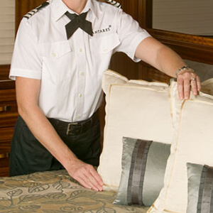 Yacht Head of Housekeeping adjusting pillows