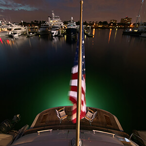 Stern view in the evening with green accent lighting and a US Flag